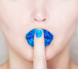 finger on blue glossy lips