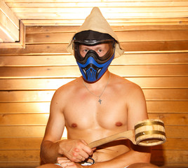 Young man sitting in Finnish bath in paintball mask