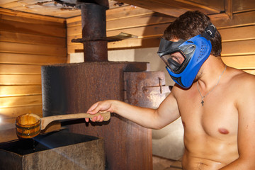 Young man sitting in sauna in paintball mask