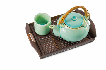 Chinese green teapot and teacups on the wooden trivet
