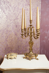 Golden candlestick with five candles on white table
