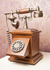 Old wooden phone. Vintage wooden telephone on white table. Retro