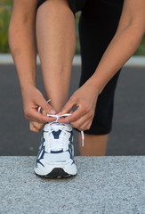 Closeup of female hands tying running shoes laces