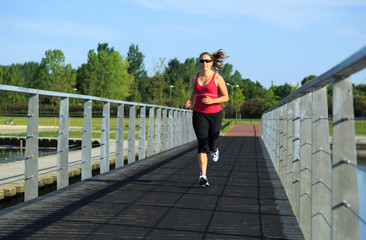 Healthy woman running on a boardwalk at a lake.