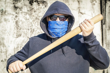 Man with a baseball bat on old wall background