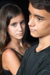 Sad teenagers - boy and girl - isolated on black