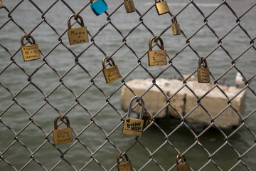 Locks with love and dedication messages on chain link fence