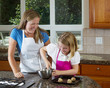 Mother watching over young daughter on how to make cookies