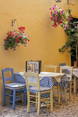 a typical Greek taverna with tables and straw chairs