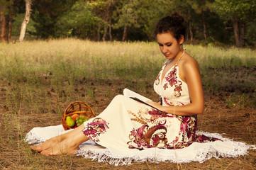 Brunette beautiful woman reading book on a meadow