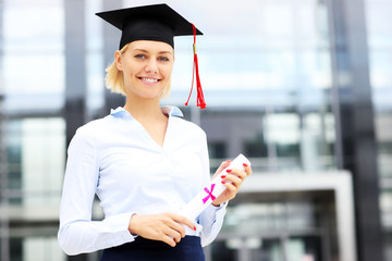 Happy graduate standing outside modern building