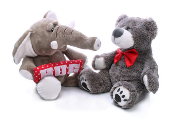 Sweet teddy bear and plush elephant on a white background