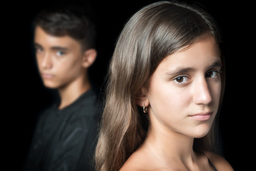 Unhappy young teen couple on a black background