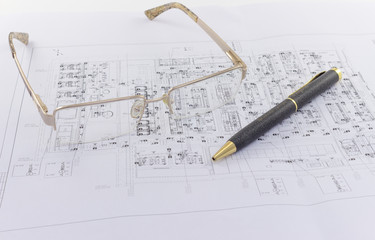 Glasses and pen lie on the engineering drawing