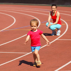 Mother & little daughter running around the stadium.