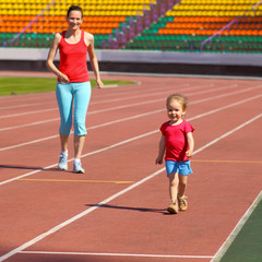 Mother & little daughter running around the stadium.