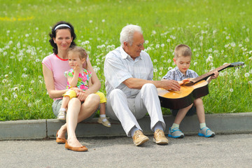 Grandfather playing guitar to his daughter and grandchildren.