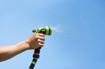 Hand holding water sprinkler against blue sky, irrigating