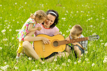 young mother plays the guitar for her young children