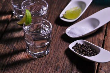 Glass of vodka shot with fresh lime on wooden table