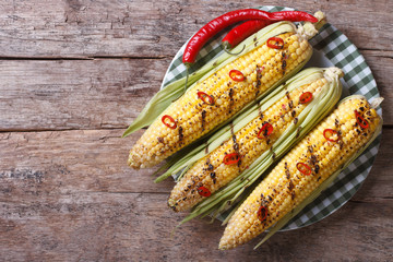 grilled corn with chili peppers a top view of a horizontal