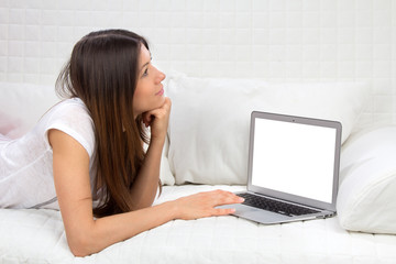 Young successful woman lying on a sofa with laptop paying bills