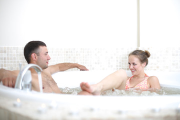 Happy beautiful couple relaxing in spa jacuzzi