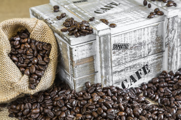 burlap bag filled with coffee beans beside old wooden box