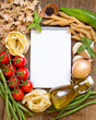 Pasta, vegetables, herbs and notebook on old wooden table