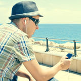 young man listening to music or talking with headphones in a sma poster