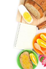 Recipe book with wholegrain bread and orange jam