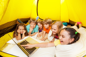 Many laughing with laptop children in a tent
