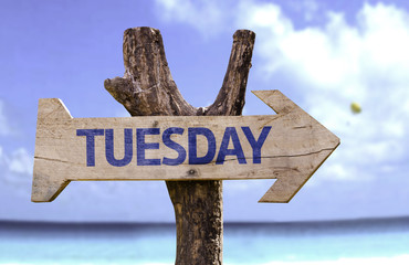 Tuesday wooden sign with a beach on background