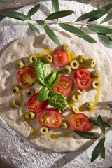 Raw pizza with tomato and olives