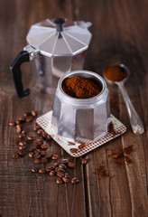 Ground coffee and coffee beans in a Moka Pot