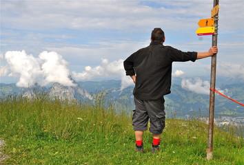 Wanderer in den Bergen lehnt an Wegweiser