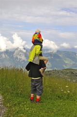 Wanderer trägt 2 Kinder auf dem Rücken
