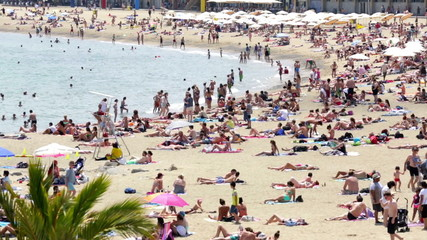 People sunbathing on sunny summer beach in Barcelona