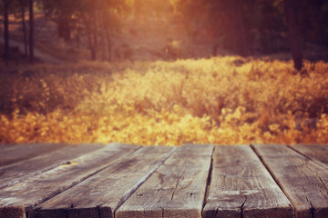 Wood board table in front of summer landscape with lens flare