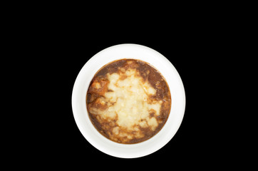 French onion soup, covered with melted cheese isolated on black