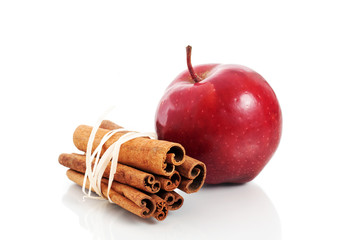 Red apple and cinnamon sticks over white background