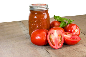 Jar of tomato sauce with tomatoes and basil