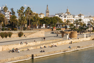 people relaxing at waterfront in Seville