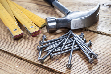 Nails, hammer and folding ruler on wooden background