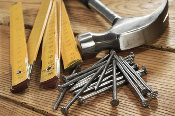 Nails, hammer and folding ruler on wood