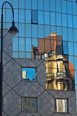 Reflection of old style buildings in a glass of Haas house