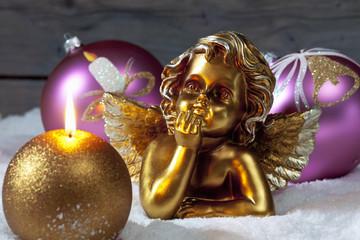Goldene Putte mit goldener Kerze und Christbaumkugeln im Schnee