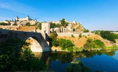 Day view of Puente de Alcantara - ancient  bridge in Toledo.