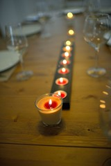 Covered dining table with wine glasses and candle