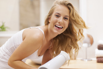 Lovely happy woman drying hair in bathroom